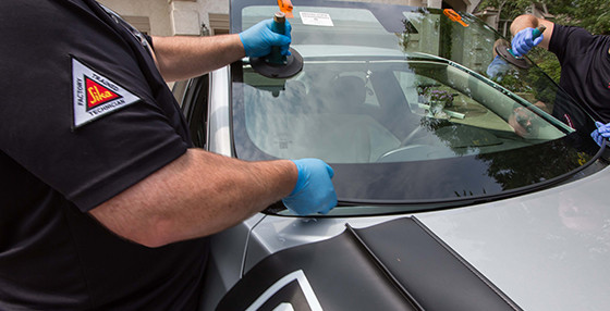 Two people replacing a windshield with auto glass windshield replacement